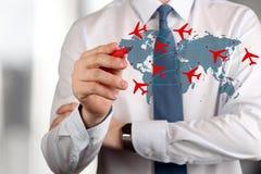 Hombre de negocios joven rutas de drenaje de un aeroplano en correspondencia de mundo Imagen de archivo