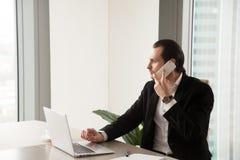 Hombre de negocios joven serio en la oficina que hace llamada de teléfono foto de archivo libre de regalías