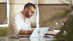 Hombre de negocios joven serio en una camisa blanca en el trabajo en la oficina El coworking interior acogedor Empleo libre almacen de video