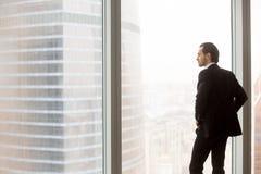 Hombre de negocios joven serio que se coloca en la oficina moderna, mirando hacia fuera fotos de archivo libres de regalías