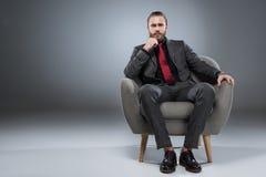 Hombre de negocios joven serio que se sienta en butaca con la mano a la barbilla y que mira a la cámara, fotos de archivo