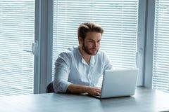 Hombre de negocios joven serio que trabaja en un ordenador portátil fotografía de archivo