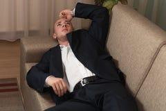 Hombre de negocios joven Sleeping en el sofá en casa foto de archivo libre de regalías