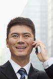 Hombre de negocios joven Smiling y el hablar en el teléfono elegante Foto de archivo