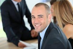 Hombre de negocios joven sonriente con el equipo Fotos de archivo