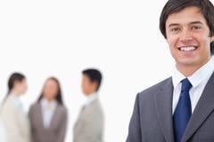 Hombre de negocios joven sonriente con el equipo detrás de él Imagen de archivo libre de regalías