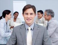 Hombre de negocios joven sonriente en una reunión Imágenes de archivo libres de regalías
