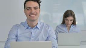 Hombre de negocios joven sonriente Looking en la cámara en oficina almacen de metraje de vídeo