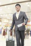 Hombre de negocios joven sonriente que camina con la maleta y celebrar el boleto del vuelo en el aeropuerto Fotos de archivo libres de regalías