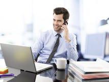 Hombre de negocios joven sonriente que habla en el teléfono móvil imagenes de archivo