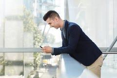 Hombre de negocios joven sonriente que se coloca con el teléfono elegante Imágenes de archivo libres de regalías
