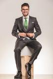 Hombre de negocios joven sonriente que se sienta en las cajas de madera Foto de archivo