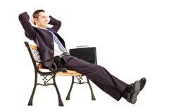 Hombre de negocios joven sonriente que se sienta en un banco y que se relaja Fotografía de archivo