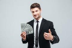 Hombre de negocios joven sonriente que sostiene el dinero y que muestra los pulgares para arriba Imágenes de archivo libres de regalías