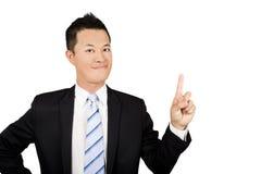 Hombre de negocios joven sonriente señalado al espacio Imagen de archivo
