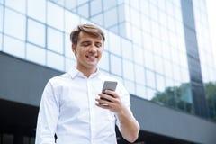 Hombre de negocios joven sonriente usando el teléfono móvil cerca del centro de negocios imagenes de archivo