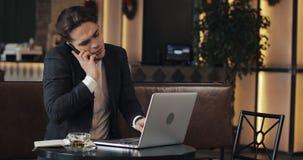 Hombre de negocios joven subrayado con el funcionamiento del ordenador portátil en el café Él que habla con el jefe habla el telé metrajes