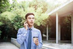 Hombre de negocios joven Talk de la motivación vía Smartphone mientras que outd del paseo imagen de archivo libre de regalías