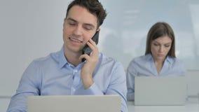 Hombre de negocios joven Talking en el teléfono, discutiendo el trabajo almacen de video