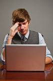 Hombre de negocios joven tensionado en la computadora portátil Imágenes de archivo libres de regalías