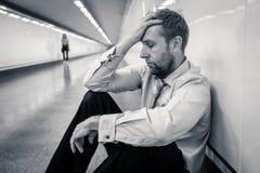 Hombre de negocios joven triste desesperado que sufre la pena del dolor emocional y la depresión profunda que se sientan solament fotos de archivo libres de regalías