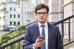 Hombre de negocios joven usando el teléfono móvil Imágenes de archivo libres de regalías