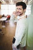 Hombre de negocios joven usando el teléfono móvil en cafetería de la oficina Fotografía de archivo