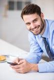 Hombre de negocios joven usando el teléfono móvil en casa Foto de archivo libre de regalías