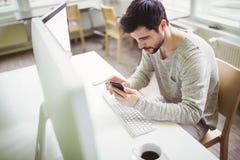 Hombre de negocios joven usando el teléfono móvil en el escritorio en oficina Imagen de archivo