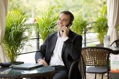 Hombre de negocios joven usando el teléfono móvil en el restaurante al aire libre Fotografía de archivo libre de regalías