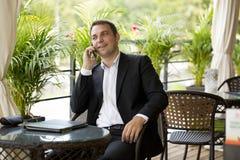 Hombre de negocios joven usando el teléfono móvil en el restaurante al aire libre Imágenes de archivo libres de regalías