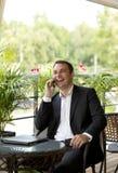 Hombre de negocios joven usando el teléfono móvil en el restaurante al aire libre Imagenes de archivo