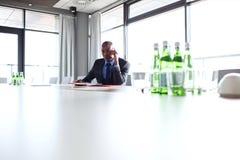 Hombre de negocios joven usando el teléfono móvil en la mesa de reuniones Fotografía de archivo libre de regalías