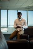 Hombre de negocios joven usando el teléfono móvil en la oficina Fotos de archivo
