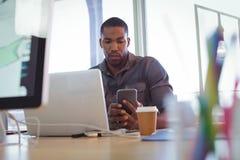 Hombre de negocios joven usando el teléfono móvil en oficina Imagenes de archivo