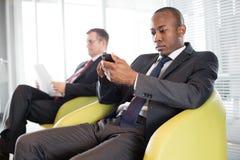Hombre de negocios joven usando el teléfono móvil en silla con el colega masculino en fondo en la oficina Imágenes de archivo libres de regalías
