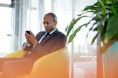 Hombre de negocios joven usando el teléfono móvil en silla en oficina Imagenes de archivo