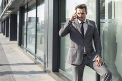 Hombre de negocios joven usando el teléfono móvil fuera de la oficina Imágenes de archivo libres de regalías