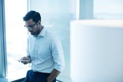 Hombre de negocios joven usando el teléfono móvil mientras que se inclina en la ventana de cristal Fotos de archivo