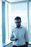Hombre de negocios joven usando el teléfono móvil mientras que se opone a la ventana de cristal Imágenes de archivo libres de regalías