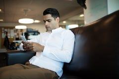 Hombre de negocios joven usando el teléfono móvil mientras que se sienta en la oficina Imagen de archivo
