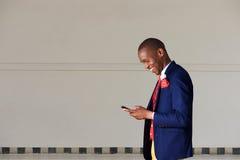Hombre de negocios joven usando el teléfono móvil y caminar al aire libre Fotografía de archivo