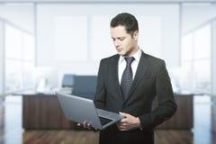 Hombre de negocios joven usando la computadora portátil Foto de archivo