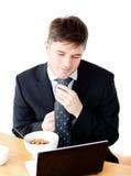 Hombre de negocios joven usando la computadora portátil durante el desayuno Foto de archivo libre de regalías