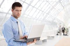 Hombre de negocios joven usando la computadora portátil en el paso Foto de archivo libre de regalías