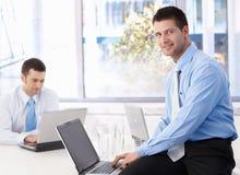 Hombre de negocios joven usando la computadora portátil que sonríe en oficina Foto de archivo