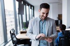Hombre de negocios joven usando la tableta digital en oficina Imagen de archivo