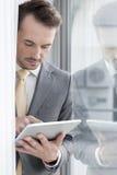 Hombre de negocios joven usando la tableta digital en oficina Fotografía de archivo