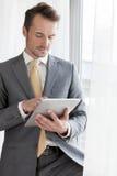 Hombre de negocios joven usando la tableta digital en oficina Fotos de archivo libres de regalías