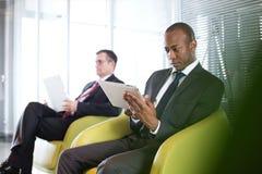 Hombre de negocios joven usando la tableta digital en silla con el colega masculino en fondo en la oficina Imagen de archivo